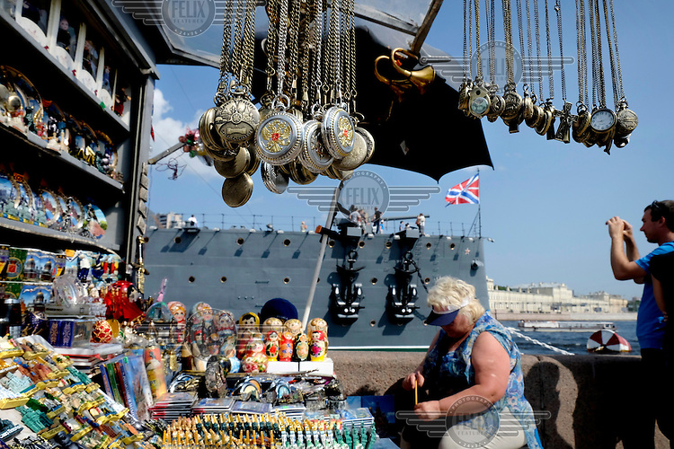 A stall selling a mix of Soviet and imperial style sailor's hats on shore in front of the Aurora battlecruiser, now a museum.  The guns of the Aurora famously announced the start of the Russian Revolution in 1917.