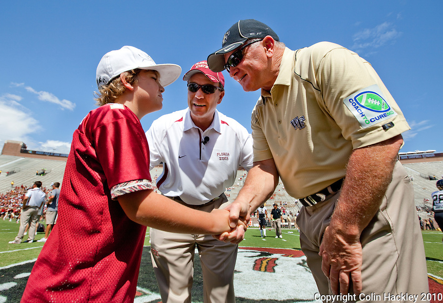 TALLAHASSEE, FL 9/25/10-FSU-WF FB10 CH-Trey Fisher, left, joins his dad Florida State Head Coach Jimbo Fisher as they greet Wake Forest Head Coach Jim Grobe prior to the game Saturday at Doak Campbell Stadium in Tallahassee. .COLIN HACKLEY PHOTO