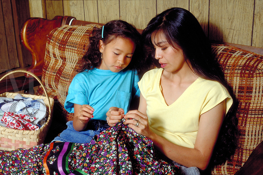Cherokee woman teaches her 10 year-old daughter to sew a traditional tear dress.  Tahlequah, OK