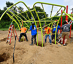 Workers adjust the positioning of the Ozark Summit Climber before filling the holes with concrete. Volunteers from the Pacific Life Foundation, Edward Jones, the Riverview Gardens School District, the Boys & Girls Clubs of Greater St. Louis and the community joined KaBOOM! and transformed an empty site into a kid-designed, state-of-the-art playground at Highland Elementary School on Saturday August 18, 2018. The playground - designed from students' drawings - will give more than 400 kids a safe place to play. KaBOOM! is a national non-profit dedicated to bringing balanced and active play into the daily lives of all kids.  Photo by Tim Vizer