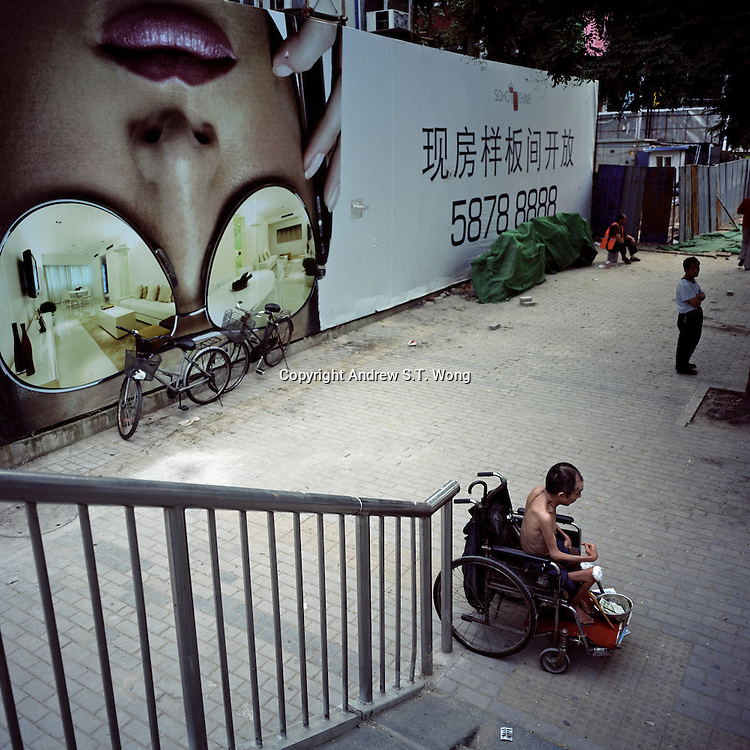 A beggar solicits money in front of a real estate advertisement in Sanlitun shopping district, Beijing, China in August, 2009. (Mamiya 6, 75mm f3.5, Kodak Ektar 160 film)