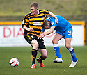 Alloa's Michael Doyle and Queen of the South's Iain Russell challenge for the ball.