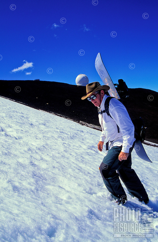 Man wearing cowboy hat and sunglasses climbs the snow covered slope of Mauna Kea volcano with his board strapped on his back.