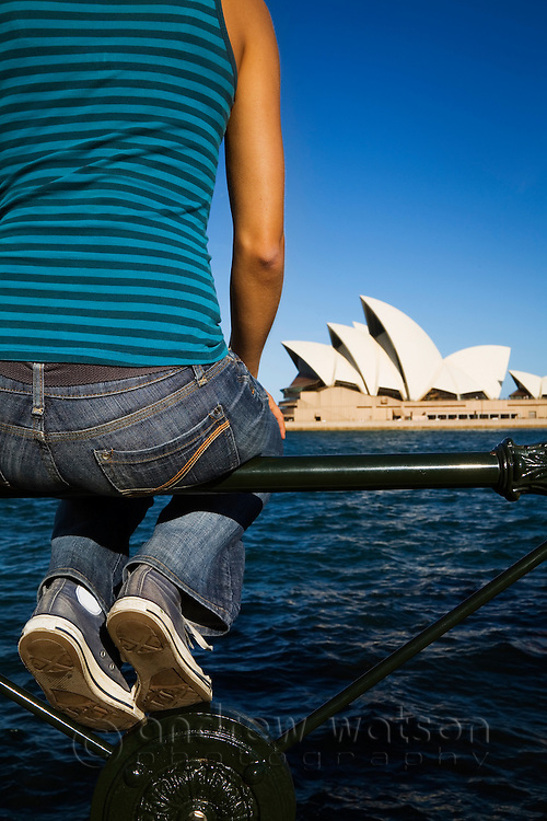 A young woman looks across Sydney harbour to the Opera House.  Sydney, New South Wales, AUSTRALIA