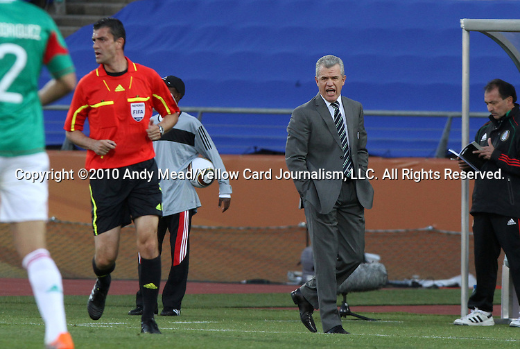22 JUN 2010: Mexico head coach Javier Aguirre (MEX) (right) yells at referee Viktor Kassai (HUN) (in red). The Mexico National Team lost 1-2 to the Uruguay National Team at Royal Bafokeng Stadium in Rustenburg, South Africa in a 2010 FIFA World Cup Group A match.