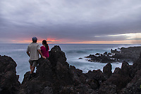 A couple enjoys a romantic sunset from lava cliffs on the Big Island of Hawai'i.