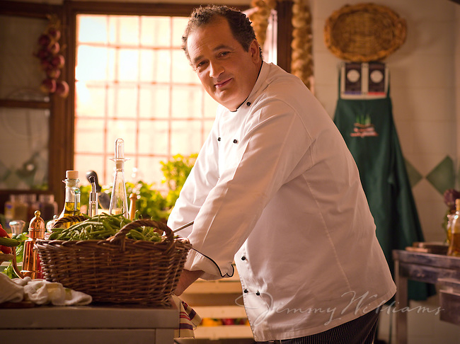 A proud Italian Chef makes authentic pesto sauce with basil and pine nuts in a beautiful Italian kitchen.