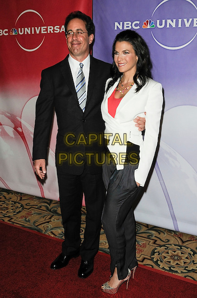 JERRY & JESSICA SEINFELD.The NBC Universal Press Tour Cocktail party at the Langham Huntington Hotel in Pasadena, California, USA..January 10th, 2010.full length glasses black suit tie white jacket husband wife married blue striped peep toe gold shoes trousers grey gray hand in pocket .CAP/ROT.©Lee Roth/Capital Pictures