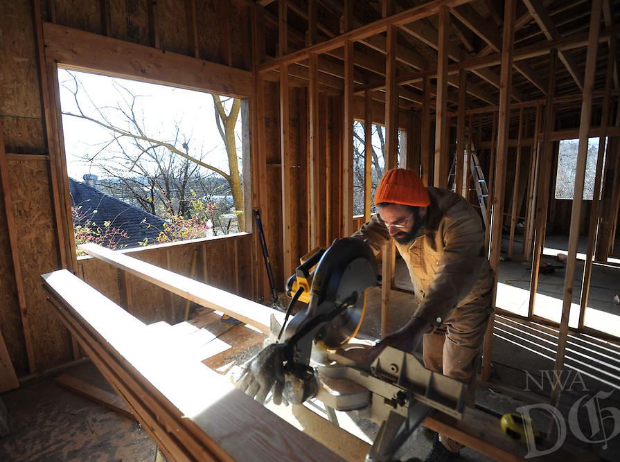 NWA Democrat-Gazette/ANDY SHUPE<br /> Dave Baer, construction manager  for Habitat for Humanity of Washington County, uses a chop saw Thursday, Dec. 8, 2016, while framing in the ceiling at the house the organization is building at 351 S. West Ave. in Fayetteville. The organization plans to host two works days Tuesday and Wednesday as a part of Habitat's Women Build program and invite women interesting in participating to come work at the site in the afternoon.