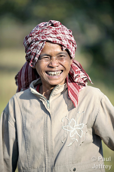 Pov Ean smiles while harvesting rice in the Cambodian village of O Kroich, where residents are members of the Kouy indigenous group. Pov Ean participates in a rice bank sponsored by the Community Health and Agricultural Development program of the Methodist Mission in Cambodia.