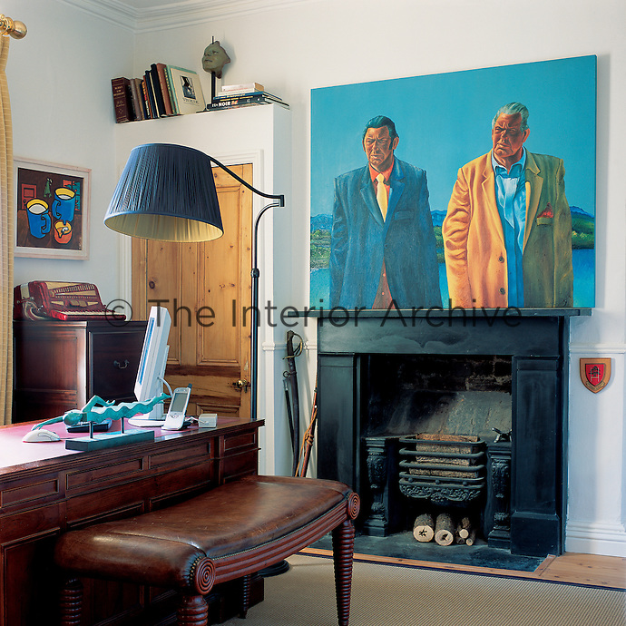 The study has a decidedly masculine air with sturdy polished wood furniture, strong contemporary paintings and a well-used fireplace