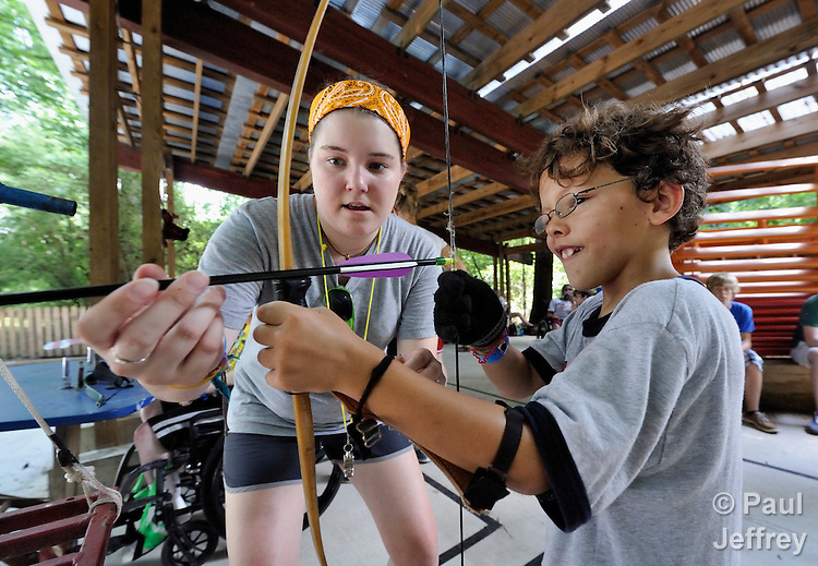 Counselor Morgan Butler helps camper Gavin Carney on the archery range at Camp Aldersgate in Little Rock, Arkansas. The camp, supported by United Methodist Women, offers children suffering from a variety of disabilities a safe and fun experience similar to that which normally-abled children often enjoy.