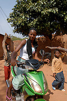 BURKINA FASO Bobo Dioulasso, old town, young modern woman with scooter in contrast children carry firewood / Burkina Faso Bobo-Dioulasso , Frau mit Motorroller