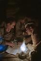 Iraq 1965    <br /> Peshmergas meeting by night in a shelter  <br /> Irak 1965 <br /> Eclair&eacute;s par une lampe a huile, rencontre de peshmergas dans un abri la nuit pendant la lutte arm&eacute;e