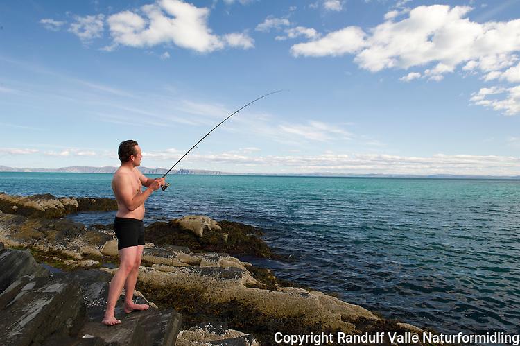 Mann fisker sei fra svaberg en varm sommerdag på 71 grader nord. ----- Man fishing from the shore a warm summer day.