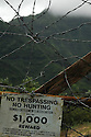 A sign and barbed wire fence  on the island of Kauai denies access.