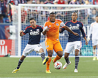 Houston Dynamo defender Jermaine Taylor (4) works to clear ball as New England Revolution midfielder Diego Fagundez (14) pressures. In a Major League Soccer (MLS) match, the New England Revolution (blue/white) defeated Houston Dynamo (orange), 2-0, at Gillette Stadium on April 12, 2014.