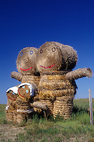 AJ0437, North Dakota, A hay bale display in shapes like people in a family in a hay field.