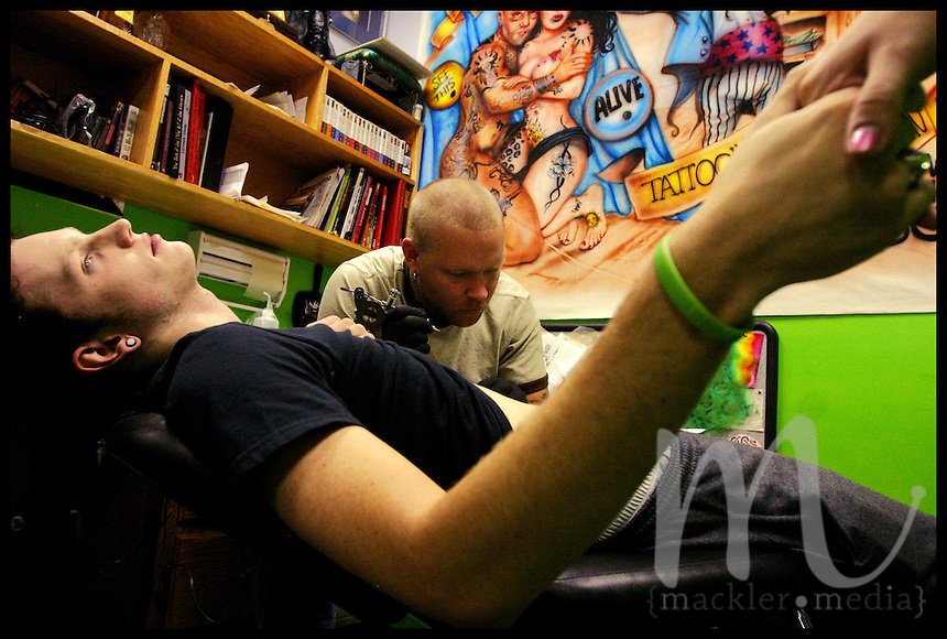 Ohio University sophomore T.J. Coffey holds on to friend Rachel Deep's hand for comfort as tattoo artist Tom American begins Coffey's tattoo in the Art Apocalypse tattoo and piercing parlor in Athens, Ohio on October 4th, 2005. This tattoo, designed by Coffey himself, is his first tattoo ever.