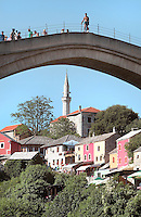Stari Most or Old Bridge, a 16th century Ottoman bridge across the Neretva river, and houses of the old town on the left bank, in Mostar, Bosnia and Herzegovina. The bridge was destroyed in the 1990s Yugoslavian war and has been rebuilt. The town is named after the mostari or bridge keepers of the Old Bridge. Mostar developed in the 15th and 16th centuries as an Ottoman frontier town and is listed as a UNESCO World Heritage Site. Picture by Manuel Cohen