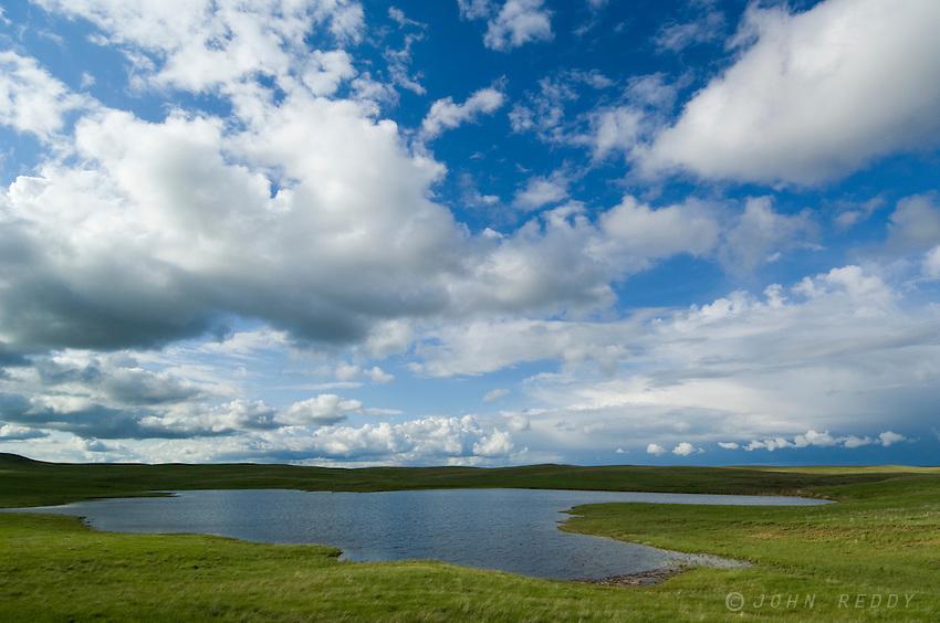 Summer sky and pond east of Baker, Montana