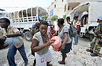 Under the watch of United Nations troops from Argentina, earthquake survivors in the quake-ravaged Haitian city of Leogane unload emergency supplies provided by Caritas Internationalis and Diakonie, a member of the ACT Alliance, on January 20. Hundreds of families in the town are homeless following a January 12 earthquake, and the two church-sponsored agencies worked together to bring them help. The aid groups organized an air cargo shipment of 34 tons of relief supplies from Europe, along with basic medicines for 80,000 people. The plane wasn't allowed to land in Port-au-Prince until January 20, yet it was unloaded within hours and aid was shipped immediately to Leogane in United Nations trucks, where it was unloaded by residents and quickly distributed.