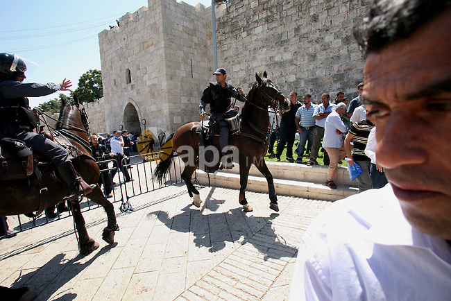 Muslim worshippers run away from Israeli mounted policemen after trying to cross a police barrier near Damascus Gate in Jerusalem's Old City during the third Friday of the holy month of Ramadan August 19, 2011. Israeli security forces declared an age limitation on Friday for Palestinians wanting to enter Jerusalem's Old City, only allowing males above the age of 50 and females above the age of 45 to enter.  Photo by MUAMMAR AWAD