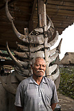 INDONESIA, Flores, Bena village, a man stands in front of his home that is adorned in cow horns that were offered to him when he built his home