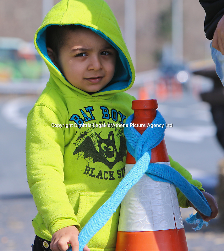 Pictured: A young migrant boy at the road block Tuesday 23 February 2016<br /> Re: Migrants on their way back to Athens have been caught by the blocked off motorway at Tembi, where local farmers have closed off the road, protesting against pension and welfare reforms near Trikala, Greece.