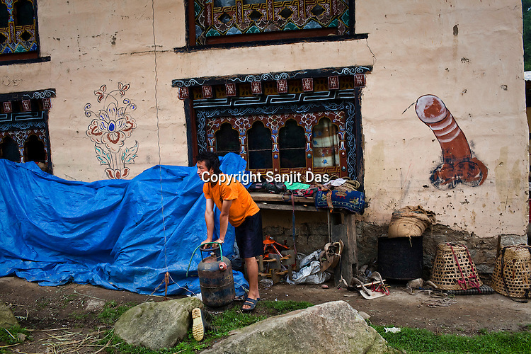 """Traditionally symbols of an erect penis in Bhutan have been intended to drive away the evil eye and are a common sight on the house walls in Bhutan as seen here in a village in Paro, Bhutan. It takes inspiration from Lama Drukpa Kunley who lived in the 15-16th century and who was popularly known as the """"Mad Saint"""" or """"Divine Madman"""" for his unorthodox ways of teaching, which amounted to being bizarre and shocking.  These explicit paintings, though embarrassing to many now can be seen painted on the walls of houses and buildings throughout Bhutan, particularly in villages, and are credited as Kunley's creations. Photo: Sanjit Das/Panos"""