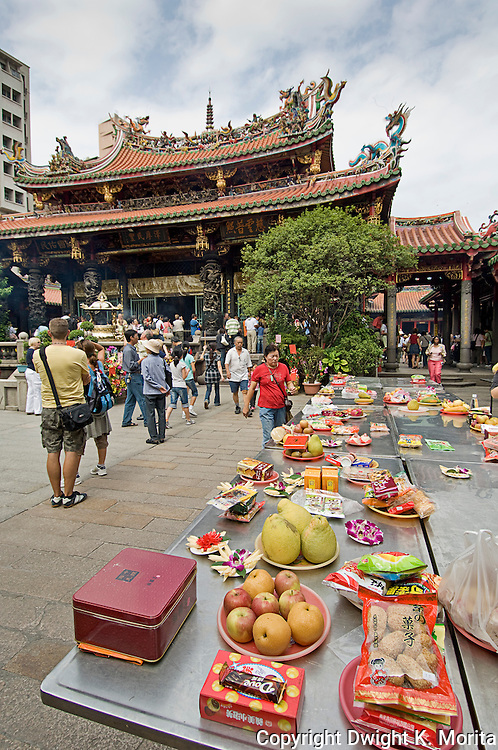 Table of food offerings is set to the side of the courtyard of Longshan Temple in Taipei