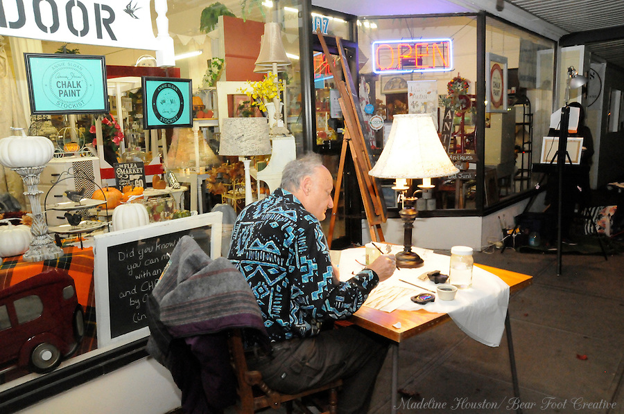 Calligraphy artist John Blackaw participates in the fall scene paint-off in front of The Attic Door during Centralia, Washington's Third Thursday on October 20, 2016.