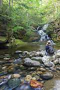 A female hiker sitting in front of Tama Fall on Snyder Brook in Randolph, New Hampshire during the summer months. This waterfall is located along the Fallsway Trail and is part of the Snyder Brook Scenic Area.