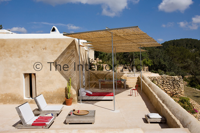 The sun-lounger and coffee table on the terrace are made from untreated local wood and the cane awning has been designed to connect the three buildings