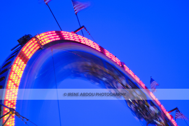 A slow shutter speed blurs the motion of the roller coaster at the Montgomery County Agricultual Fair in Gaithersburg, Maryland.  This image is a composite of three photographs taken at shutter speeds of 1/30, 0.6, and 3.2 seconds.