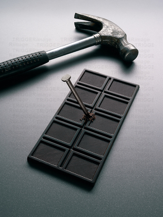 A hammer and a nail through a bar of chocolate
