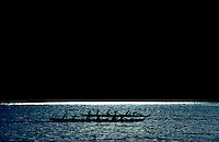 Silhouetted outrigger canoes racing on silvery blue water against a black sky.