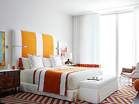 A bold, bright guest bedroom is decorated in white and tones of orange. Strong geometric patterns give the room a retro feel.
