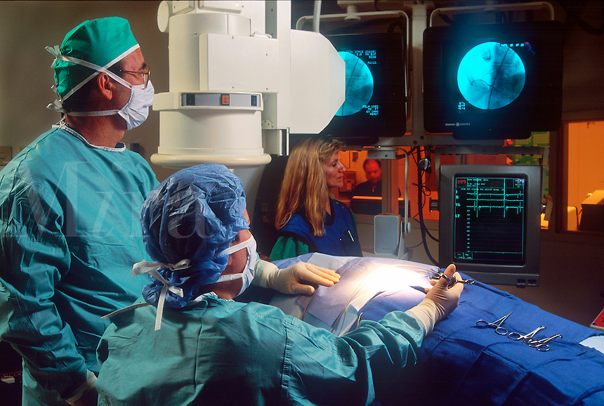 Two surgeons perform a cardiac catheterization procedure in a hospital.