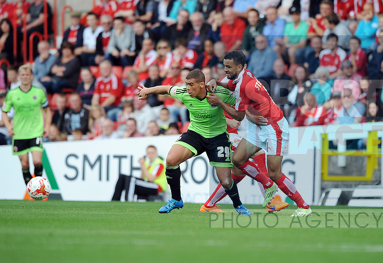 Che Adams of Sheffield United is challenged by Kevin Stewart of Swindon Town<br /> - English League One - Swindon Town vs Sheffield Utd - County Ground Stadium - Swindon - England - 29th August 2015 <br /> --------------------