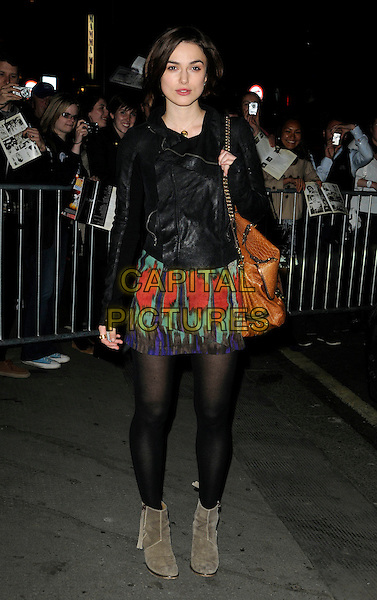 """KEIRA KNIGHTLEY.Seen leaving the evening performance of """"The Children's Hour"""", Comedy Theatre, London, England, UK, .27th 2011..full length red ikat print blue green  black tights  leather jacket brown mulberry bag satchel .CAP/CAN.©Can Nguyen/Capital Pictures."""