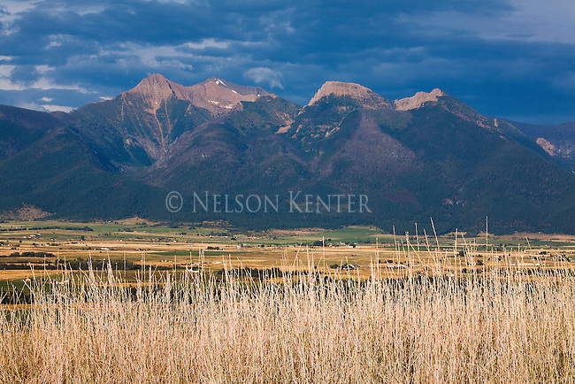 The Mission Mountains and a dark blue sky with the Mission Valley in the foreground near St. Ignatiuis, Montana
