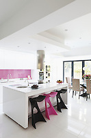 Spray-painted units and porcelain floor tiles reflect the light in this airy kitchen
