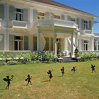 Tiny wrought-iron sculptures of fairies dance across the lawn before the classical facade of this new South African property