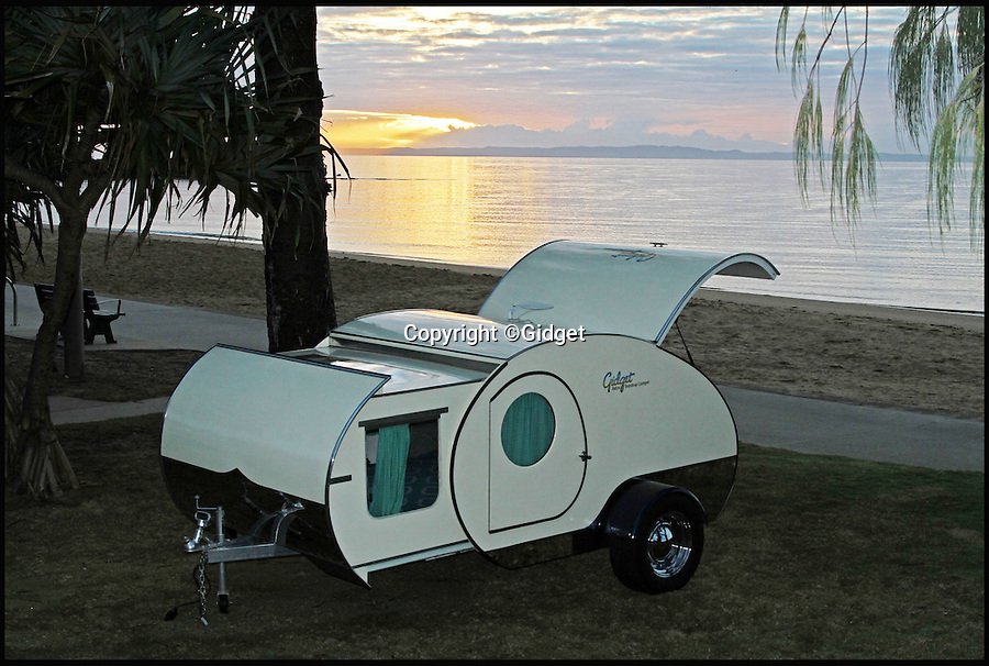 BNPS.co.uk (01202 558833)<br /> Pic: Gidget/BNPS<br /> <br /> This miniature caravan might look better suited to 'cramping' than 'glamping' but despite its diminutive size it still boasts a full size double bed and a fully-equipped kitchen.<br /> <br /> The Tardis-like creation is taking campsites by storm this summer because at just 8ft long it is so small it can be towed like a trailer on holidays and weekend getaways.<br /> <br /> But its nifty design hides a secret compartment that slides out to almost double the living space in less than 30 seconds, meaning it can comfortably sleep two adults with room to spare.<br /> <br /> The retro-looking pod reveals a luxurious living space packed with mod cons including a rotating entertainment unit with a 24-inch flatscreen TV and stereo system with surround sound. <br /> <br /> The caravan, called a Gidget, will set buyers back around £10,000.