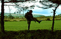 British Army soldiers on armed foot patrol in the countryside of Northern Ireland. The soldier is crossing barbed wire fencing instead of gates and natural openings which may be booby-trapped. This image may only be used to portray the subject in a positive manner..©shoutpictures.com..john@shoutpictures.com