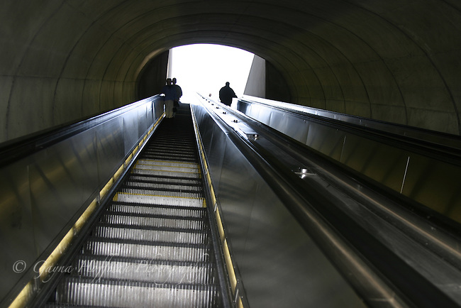 People at top of subway escalator.
