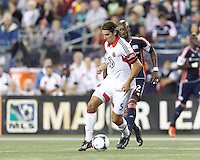 D.C. United defender Dejan Jakovic (5) dribbles at midfield as New England Revolution forward Dimitry Imbongo (92) closes. In a Major League Soccer (MLS) match, the New England Revolution (blue) defeated D.C. United (white), 2-1, at Gillette Stadium on September 21, 2013.