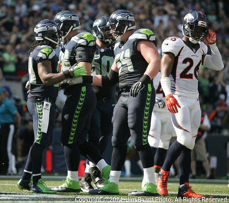 Seattle Seahawks  running back Marshawn Lynch (24) is greeted by teammates after scoring a touchdown on a five yard pass from Russell Wilson against the Denver Broncos in the second quarter at CenturyLink Field in Seattle, Washington on September 21, 2014. The Seahawks won 26-20 in overtime.    ©2014. Jim Bryant Photo. All rights Reserved.