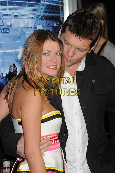 Crystal Humphries & Sam Worthington.L.A. Premiere of  'Man on a Ledge' held at The Grauman's Chinese Theatre in Hollywood, California, USA..January 23rd, 2012 .half length pink yellow white striped stripes strapless dress grey gray jacket couple shirt side looking down.CAP/ADM/BP.©Byron Purvis/AdMedia/Capital Pictures.